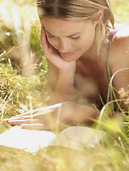 Aug. 23, 2007 - Woman lying in grass reading a book and smiling.. Model & Property Released (MR&PR) (Credit Image: © Cultura/ZUMAPRESS.com)