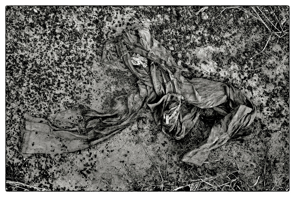 "A pair of mud-encrusted trousers lie half-buried in the mud on farmland located in the Chaiyaphum Province of Northeast Thailand, 2013. From the series: ""Pha Koeng"" (2011-2017)."