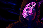 Hooded man wearing a glowing opera mask.Black light