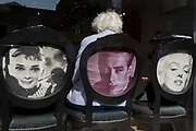 An elderly lady seated on a chair featuring Hollywood movie stars Audrey Hepburn, James Dean and Marylin Monroe, waits her turn in a local hairdressers, on 2nd October 2019, in Sutton, London, England