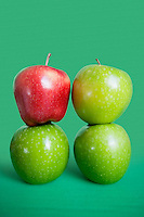 Stack of red and green apples over colored background