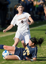 West Virginia Mountaineers defender Nicole Mailloux (13) slide tackles the ball from Virginia Cavaliers forward Lauren Alwine (9).  The #16 ranked Virginia Cavaliers defeated the #12 ranked West Virginia Mountaineers 3-2 in the second round of NCAA Division 1 Women's Soccer Tournament at Klockner Stadium on the Grounds of the University of Virginia in Charlottesville, VA on November 16, 2008.