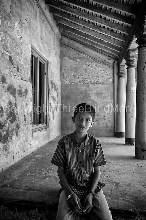 Boy seated on the thinnai (raised platform) of a home in Nagore.<br /> Tamil Nadu state. South India.