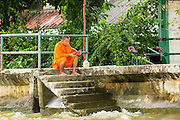 "17 NOVEMBER 2012 - BANGKOK, THAILAND:  A Buddhist monk reads a book at a boat landing in the Thonburi section of Bangkok. Bangkok used to be known as the ""Venice of the East"" because of the number of waterways the criss crossed the city. Now most of the waterways have been filled in but boats and ships still play an important role in daily life in Bangkok. Thousands of people commute to work daily on the Chao Phraya Express Boats and fast boats that ply Khlong Saen Saeb or use boats to get around on the canals on the Thonburi side of the river. Boats are used to haul commodities through the city to deep water ports for export.    PHOTO BY JACK KURTZ"