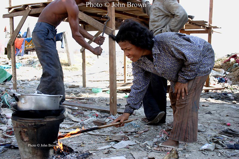 A worker from The Stung Meanchey Landfill in Phnom Penh, Cambodia, cooks a family meal as her husband (back left) and a neighbor build a new home for their family of seven.