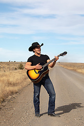cowboy on a dirt road singing and playing a guitar