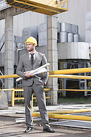Full length of young male engineer holding blueprints outside industry