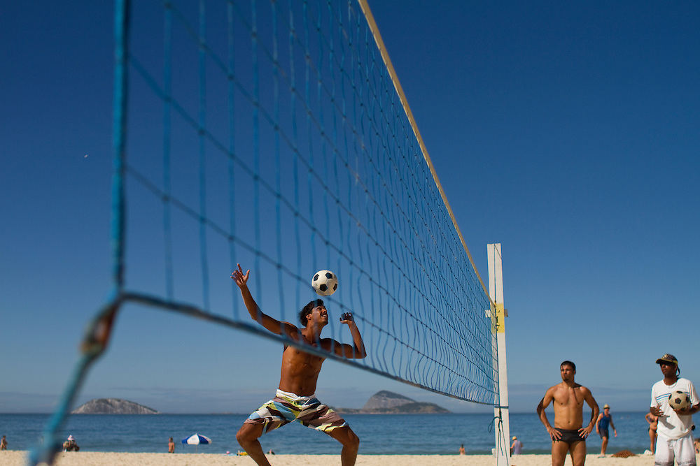 "RIO DE JANEIRO, BRAZIL: Young men playing ""futebol"" -a mixture of football and volleyball- at Ipanema beach."
