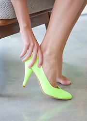Woman Putting on Pastel Green Shoe, Close-up View