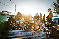 JEROME A. POLLOS/Press..Carburetor stacks and valve colors catch the setting sunlight as visitors to the River City Rod Run Friday walk past the line of cars on display.