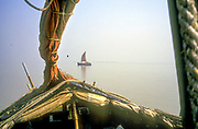 Boats transporting sand, sail on the Bay of Bengal, India.