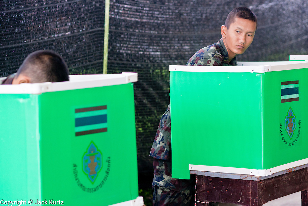 26 JUNE 2011 - CHIANG MAI, THAILAND: Royal Thai Army soldiers mark their absentee ballots at the voting center in Chiang Mai, Thailand, Sunday. The role of the military in this election has been fiercely debated because the Army command has indicated they would not favor a victory by Pheua Thai, the leading party in this election. Absentee voting was Sunday, July 26 in Thailand's national election. The regular voting is Sunday July 3. In Chiang Mai, center of the powerful Red Shirt opposition movement and their legal party Pheua Thai, turnout was heavy despite a steady rain. Thailand's democracy will be tested in the election, which is the most bitterly fought contest in Thai political history. The Pheua Thai represents people loyal to fugitive former Prime Minister Thaksin Shinawatra, ousted by a military coup in 2006. The ruling Democrats have governed Thailand in one form or another nearly continuously since 1932. Pre-election polls show Pheua Thai leading but not by enough to rule without forming a coalition with smaller parties.      PHOTO BY JACK KURTZ
