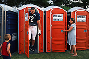 To the surprise of a pair of Chicago Bears' fans, 1st round draft choice Gabe Carimi exits a portable toilet during the middle of a training camp practice at Olivet Nazarene University in Bourbonnais, IL on Monday, August 1, 2011. The rookie, from the University of Wisconsin, was unaware that the players had their own separate bathroom facilities.