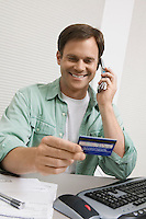 Man Using Credit Card to Order Over Phone