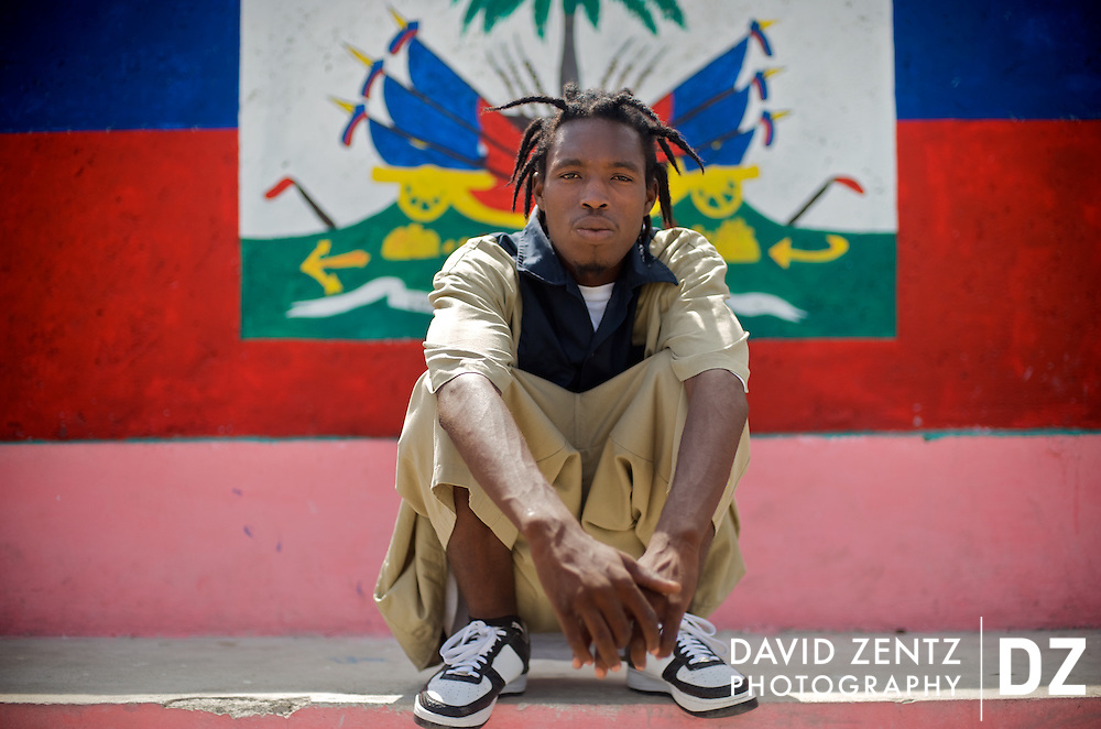 2Double displays his national pride in front of a mural of the Haitian flag near his home in the infamous Cite Soleil slum in Port-au-Prince, Haiti on July 19, 2008.