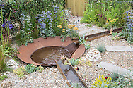 Corten steel rill water feature running into large bowl, with gravel and naturalistic drought-tolerant planting