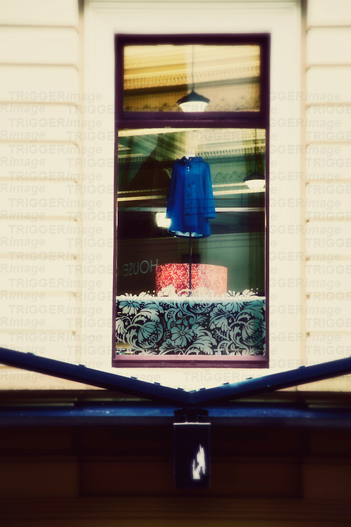 Vertical image of a shop window featuring a womens blue coat