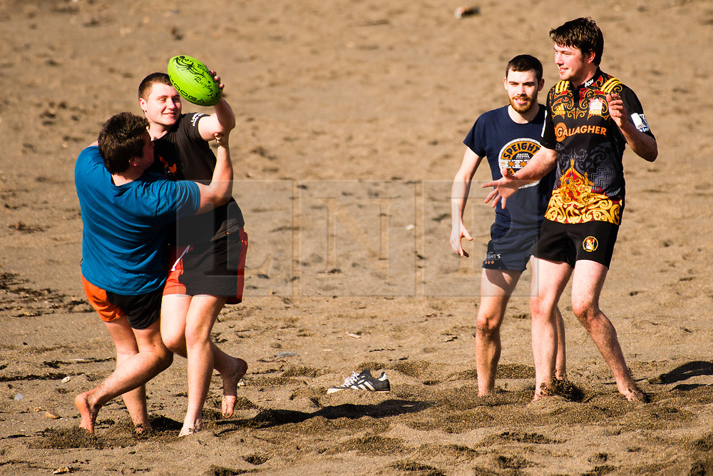 © Licensed to London News Pictures. 15/03/2017. Aberystwyth, UK. A group of young men enjoying a game of beach rugby the very warm spring afternoon  sunshine on the beach and promenade in Aberystwyth  on the Cardigan Bay coast of Ceredigion, West Wales. Photo credit: Keith Morris/LNP