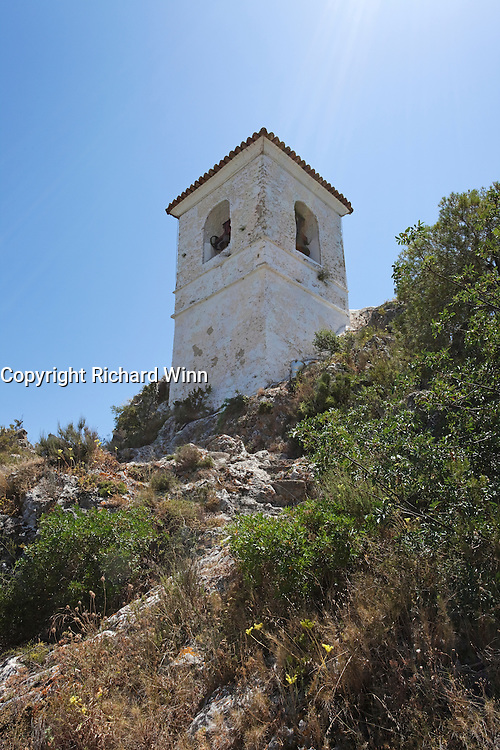 Sun rays shining on the bell tower of Castell d'Alcozaiba, in Guadalest, Alicante, Spain.