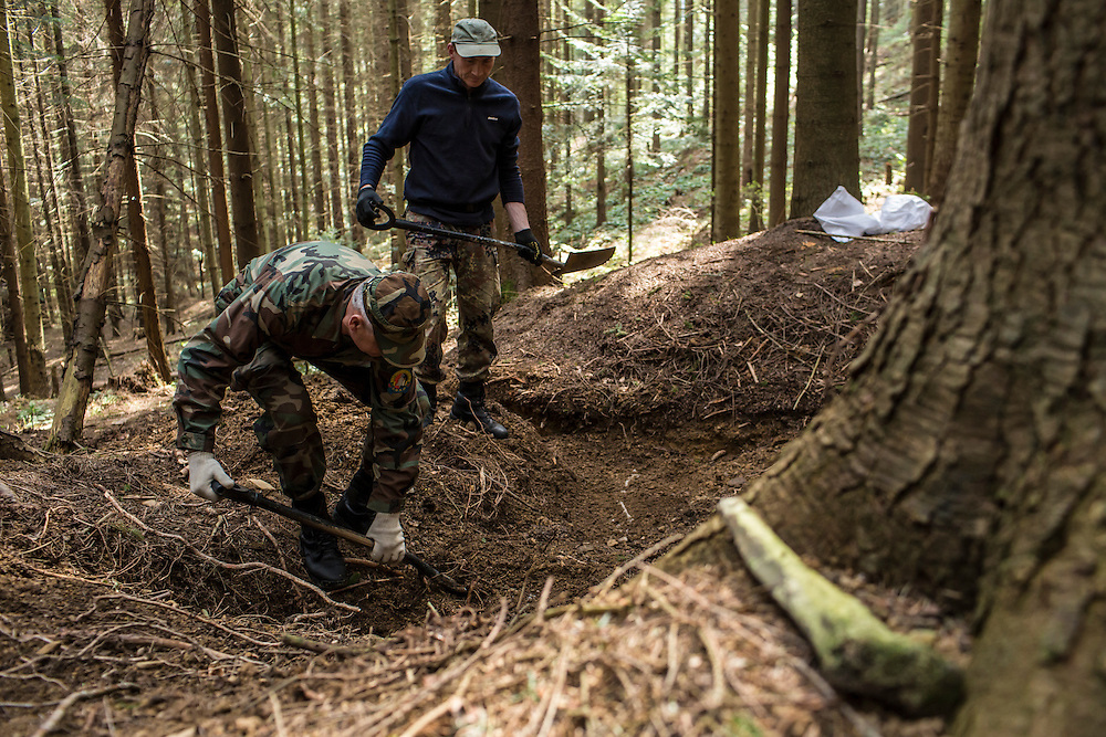 SKOLE, UKRAINE - MAY 1, 2015: A human tibia sits on the ground as Volodymyr Kharchuk, left, and Ostap Kozak, deputy director and archivist of the organization Dolya, respectively, dig at a World War II-era mass grave believed to contain the remains of Ukrainian partisans in Skole, Ukraine. Dolya was formed to excavate and repatriate remains from World War II, though its focus is often on locating the graves of Ukrainian partisans killed by Soviet forces. CREDIT: Brendan Hoffman for The New York Times