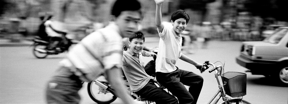 Boys on bikes rushing by waving