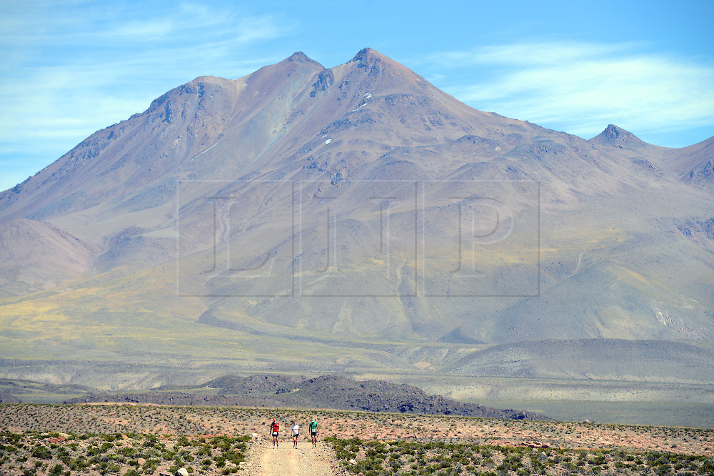 © Licensed to London News Pictures. 14/11/2013.<br /> <br /> Competitors during the race. <br /> <br /> Inaugural Volcano Marathon, Atacama Desert, Chile. The race took place in the Atacama Desert in Chile, beginning at an altitude of 4,400 metres (14,500 feet) in the vicinity of Lascar Volcano. It was a gruelling affair for many of the competitors who had to encounter some challenging hills and manage the impact of the heat and oxygen deprivation. The average altitude of the entire race was close to 4,000 metres and temperatures reached the mid 20s Celsius, or almost 80 Degrees Farenheit.<br /> <br /> Photo credit : Mike King/LNP<br /> <br /> Further information and link to video here: https://www.dropbox.com/s/0277bepxvo0t8il/Marathon%20copy.txt