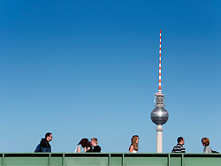 People crossing modern footbridge across Spree River in Mitte Berlin with famous TV Tower to rear