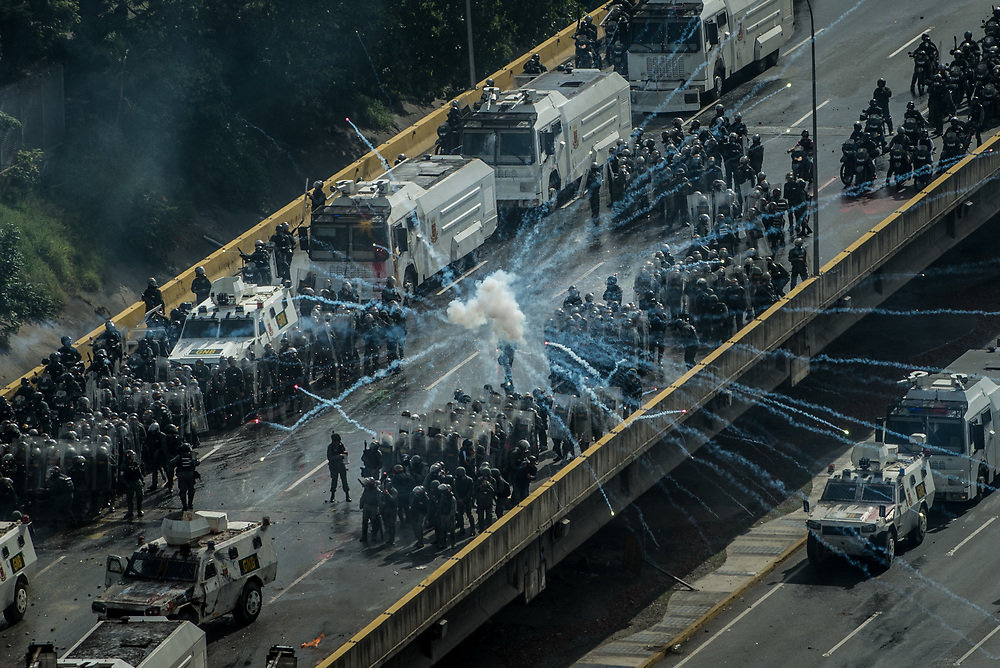 """CARACAS, VENEZUELA - MAY 27, 2017:  Anti-government protesters fire fireworks from what they call a """"torta"""" (a big box of fireworks) at National Guard soldiers who responded by heavily tear gassing and firing rubber bullets and buckshot at them. The streets of Caracas and other cities across Venezuela have been filled with tens of thousands of demonstrators for nearly 100 days of massive protests, held since April 1st. Protesters are enraged at the government for becoming an increasingly repressive, authoritarian regime that has delayed elections, used armed government loyalist to threaten dissidents, called for the Constitution to be re-written to favor them, jailed and tortured protesters and members of the political opposition, and whose corruption and failed economic policy has caused the current economic crisis that has led to widespread food and medicine shortages across the country.  Independent local media report nearly 100 people have been killed during protests and protest-related riots and looting.  The government currently only officially reports 75 deaths.  Over 2,000 people have been injured, and over 3,000 protesters have been detained by authorities.  PHOTO: Meridith Kohut"""