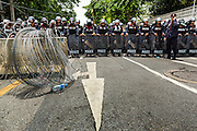 07 AUGUST 2013 - BANGKOK, THAILAND:    Thai riot police deployed to prevent anti-government protesters from going to the Parliament building. About 2,500 protestors opposed to an amnesty bill proposed by Thailand's ruling party marched towards the Thai parliament in the morning. The amnesty could allow exiled fugitive former Prime Minister Thaksin Shinawatra to return to Thailand. Thaksin's supporters are in favor of the bill but Thai Yellow Shirts and government opponents are against the bill. Thai police deployed about more than 10,000 riot police and closed roads around the parliament. Although protest leaders called off the protest rather than confront police, a few people were arrested for assaulting police when they tried to break through police lines. Several police officers left the scene under medical care after they collapsed in the heat.  PHOTO BY JACK KURTZ