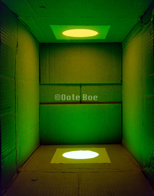 cardboard box with a mixture of green and yellow light shining in it