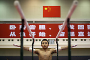 A young man on China's national gymnastics team warms up before training in Beijing. China has ordered its national gymnasts to turn in their computers and car keys, turn off their cell phones at 10 p.m. and stay in at night, so they will be fresh for training the next day. Members of the men's team would also have to give up their habit of playing soccer to blow off steam.