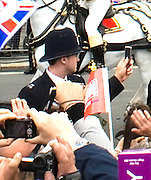 29.APRIL.2011. LONDON<br /> <br /> POLICE OFFICER AT THE ROYAL WEDDING BETWEEN PRINCE WILLIAM AND CATHERINE MIDDLETON TAKING A PICTURE ON A MOBILE PHONE OF THE ROYAL CARRIAGE HEADING TO BUCKINGHAM PALACE IN LONDON<br /> <br /> BYLINE: EDBIMAGEARCHIVE.COM<br /> <br /> *THIS IMAGE IS STRICTLY FOR UK NEWSPAPERS AND MAGAZINES ONLY*<br /> *FOR WORLD WIDE SALES AND WEB USE PLEASE CONTACT EDBIMAGEARCHIVE - 0208 954 5968*