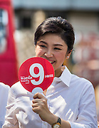 17 FEBRUARY 2013 - BANGKOK, THAILAND:  Thai Prime Minister YINGLUCK SHINAWATRA campaigns for Pongsapat Pongchareon in Bangkok Sunday. Pol General Pongsapat Pongcharoen, a former deputy national police chief who also served as secretary-general of the Narcotics Control Board is the Pheu Thai Party candidate in the upcoming Bangkok governor's election. Nine is Pongsapat's number on the ballot. (He resigned from the police force to run for Governor.) Former Prime Minister Thaksin Shinawatra reportedly recruited Pongsapat. Most of Thailand's reputable polls have reported that Pongsapat is leading in the race and likely to defeat Sukhumbhand Paribatra, the Thai Democrats' candidate and incumbent. The loss of Bangkok would be a serious blow to the Democrats, whose base is the Bangkok area.     PHOTO BY JACK KURTZ