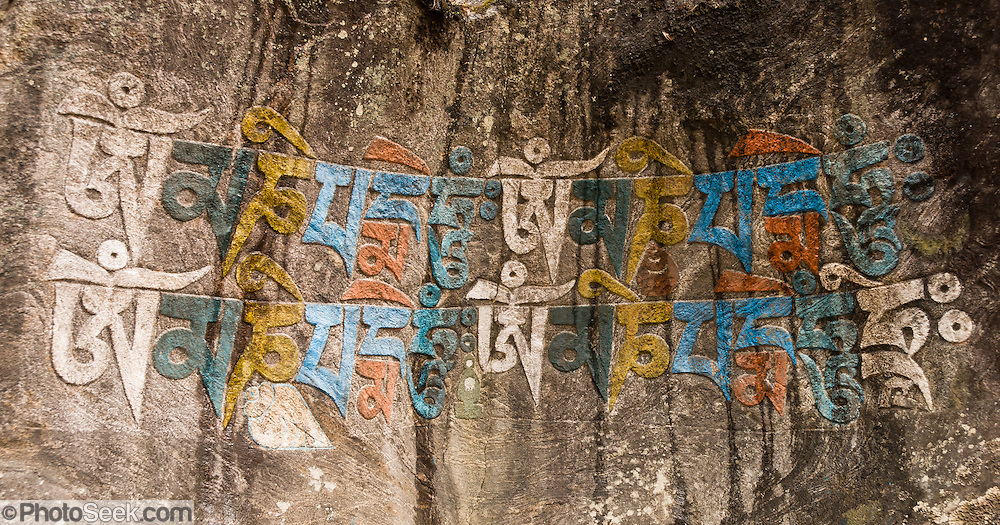 "In the Everest Area of Nepal: These 4 Tibetan ""Om Mani Padme Hum"" repetitions invoke compassion. Om Mani Padme Hum means ""Hail to the jewel in the lotus"". Mani stones are stone plates, rocks and/or pebbles inscribed, usually with mantra or shtamangala, as a form of prayer in Tibetan Buddhism. Out of respect, people should walk to the left or clockwise around Mani Walls. Mani stones are placed in mounds or cairns along roadsides and rivers as an offering to spirits of place (or genius loci)."