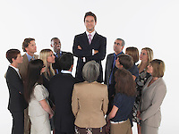 Group of Businesspeople Staring at Tall Man