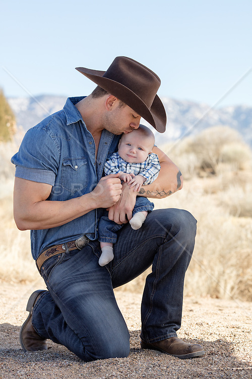 cowboy kneeling down and kissing a baby on the forehead