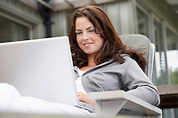 Woman using laptop sitting on porch half length