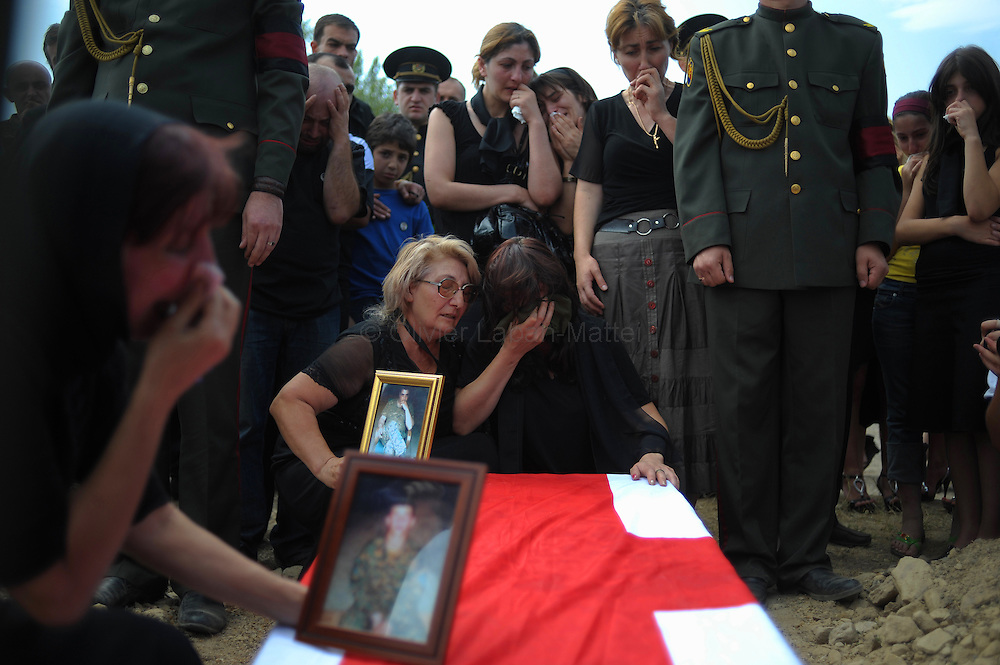 A woman cries on the Georgian-flag draped coffin of her husband, a Georgian soldier killed in South Ossetia duirng the conflict with Russia on August 30, 2008 during military funerals in Mukhadgverdi, west of Tbilisi. Russian President Dmitry Medvedev called Saturday on European governments to send more observers to Georgia, a Kremlin statement said.