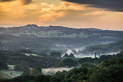 © Licensed to London News Pictures. 25/08/2015. Saltaire, UK. Picture shows early morning fog rising from the Leeds to Liverpool canal in Shipley seen from Baildon Moor. Yorkshire woke to bright sunshine this morning although a cloudy afternoon is expected. Photo credit: Andrew McCaren/LNP