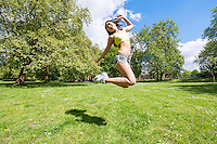 Full length of happy fit woman jumping in park
