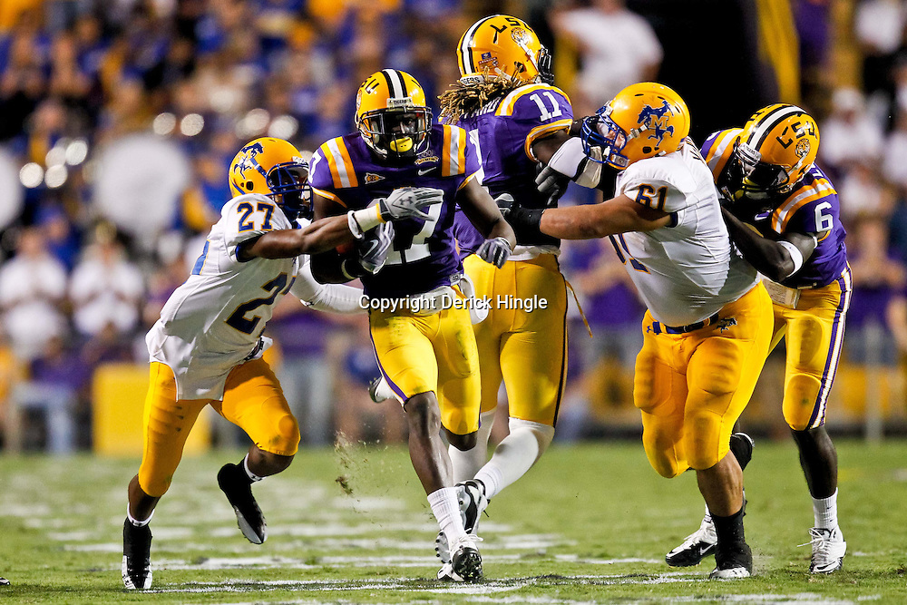 October 16, 2010; Baton Rouge, LA, USA; LSU Tigers cornerback Morris Claiborne (17) returns a interception as McNeese State Cowboys wide receiver Diontae Spencer (27) attempts to make a tackle during the second half at Tiger Stadium. LSU defeated McNeese State 32-10. Mandatory Credit: Derick E. Hingle