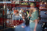 Commuters to-and-fro in the heat of a city summer during a 3-day underground tube strike in September 2007. This is Victoria mainline station during a summer heatwave. It's a transport hub for tube lines, buses and overground train routes and we see masses of pedestrians and buses reflected in the glass of a bush shelter window. As a result of the industrial action, the buses are full so the quickest way of reaching one's destination is to walk. An official points out directions, someone shields his eyes from the sun, a lady walks with her hands in pockets, the 239 bus to Victoria approaches and sightseeing tours sign advertises tickets. People are seen in differing scales and sizes.