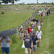Thousands of visitors to Gettysburg National Military Park crossed the fields to participate in the Pickett's Charge Commemorative March, during the Sesquicentennial Anniversary of the Battle of Gettysburg, Pennsylvania on Wednesday, July 3, 2013.  The march was an opportunity to follow in the footsteps of the Confederate soldiers by walking with living historians and park rangers along the path of the famously ill-fated Pickett's Charge, which brought to a close The Battle of Gettysburg when the Union Army repelled their advance. The Battle of Gettysburg lasted from July 1-3, 1863 resulting in over 50,000 soldiers killed, wounded or missing.  John Boal Photography