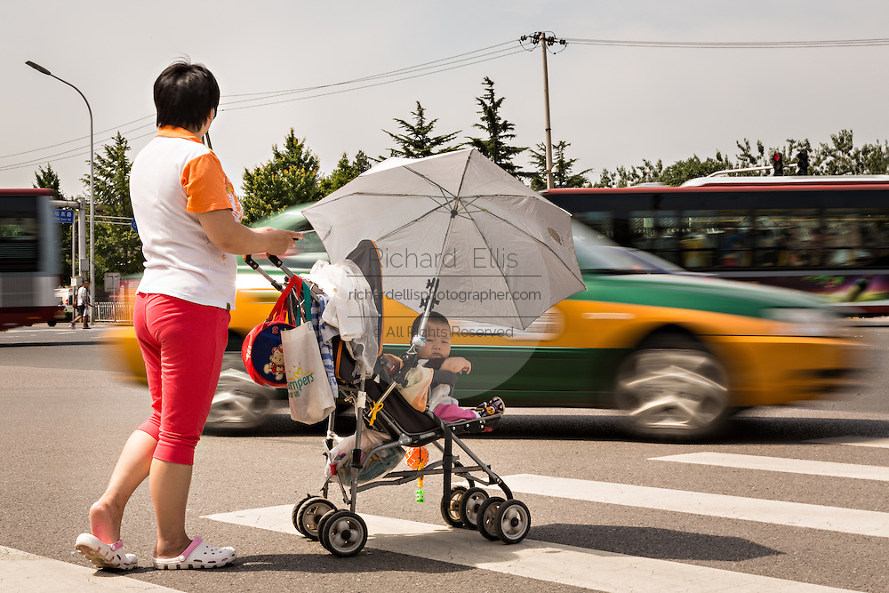 A Chinese woman pushing a baby carriage waits for traffic to cross a busy road during summer in Beijing, China