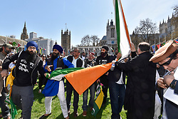 © Licensed to London News Pictures. 18/04/2018. LONDON, UK. Kashmiri and Sikh demonstrators pull down the Indian flag in Parliament Square in protest against the regime of Indian Prime Minister Narendra Modi.  Sikhs, Kashmiri muslims and other groups all had their own message against PM Modi who is visiting London to take part in the Commonwealth Heads of Government 2018 summit. Parliament Square has been decorated with flags of countries of the Commonwealth. Photo credit: Stephen Chung/LNP