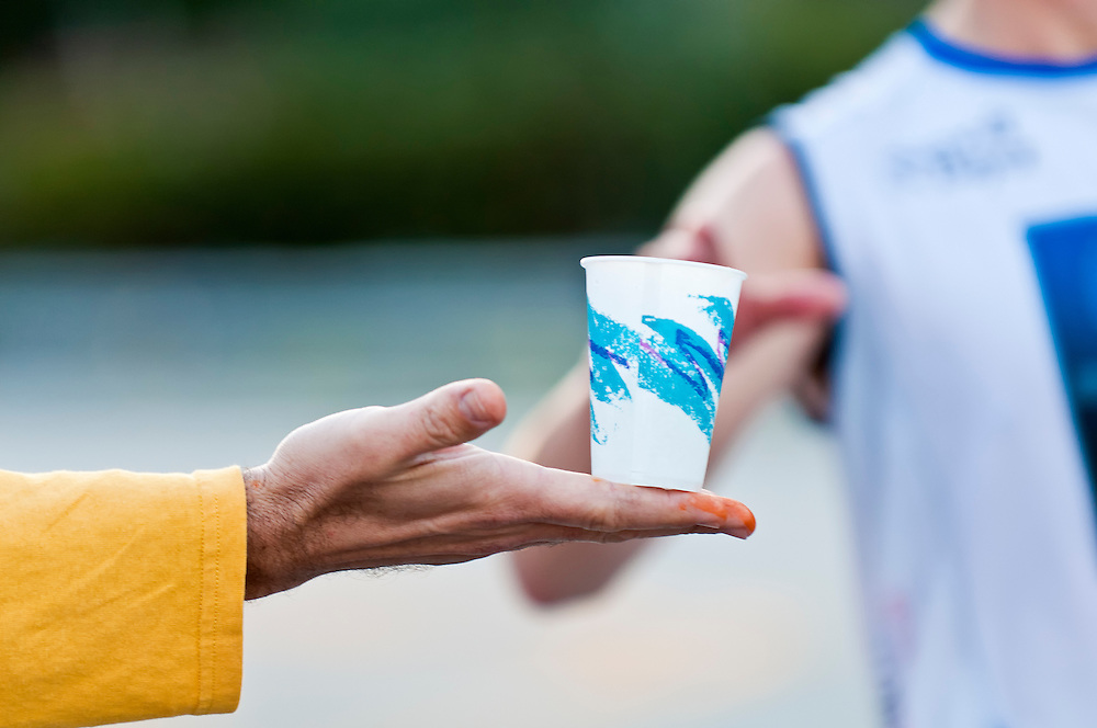 Volunteers hands offering water during a Marathon. Use of selective focus. Lots of Copyspace.