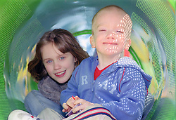 Brother and sister sitting together inside tunnel in playground smiling,