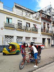 Old Havana, Cuba. Havana vieja, street. taxi driver, pedal taxi, yellow coco taxi.