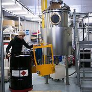Dr Anne Brock handles the drum of 200l alcohol used for making the next batch of Jensen's Gin. <br /> <br /> Bermondsey Distillery, the makers of Jensen's Gin. Bermondsey Gin is established and owned by Christian Errboe Jensen. <br /> <br /> Bermondsey Distillery, kendt for deres Jensen's Gin, startet og ejet af danskeren  Christian Jensen.  Dr. Anne Brock håndterer tønden med 200l alkohol der bruges i destilleringen.