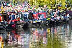 Little Venice, London, May 1 2016. Bright sunshine greets narrow boaters at the Inland Waterways Association's annual Canalway Cavalcade, a get-together of narrow boaters from all over the UK, on the May Day bank holiday. PICTURED: Colourful bunting, a blue sky and ornately painted narrowboats create colourful reflections. &copy;Paul Davey<br /> FOR LICENCING CONTACT: Paul Davey +44 (0) 7966 016 296 paul@pauldaveycreative.co.uk